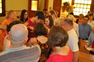 Members of Whitehall Mennonite Church pray over Danilo Sanchez
