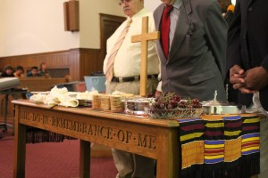 Church elders pray behind the communion table